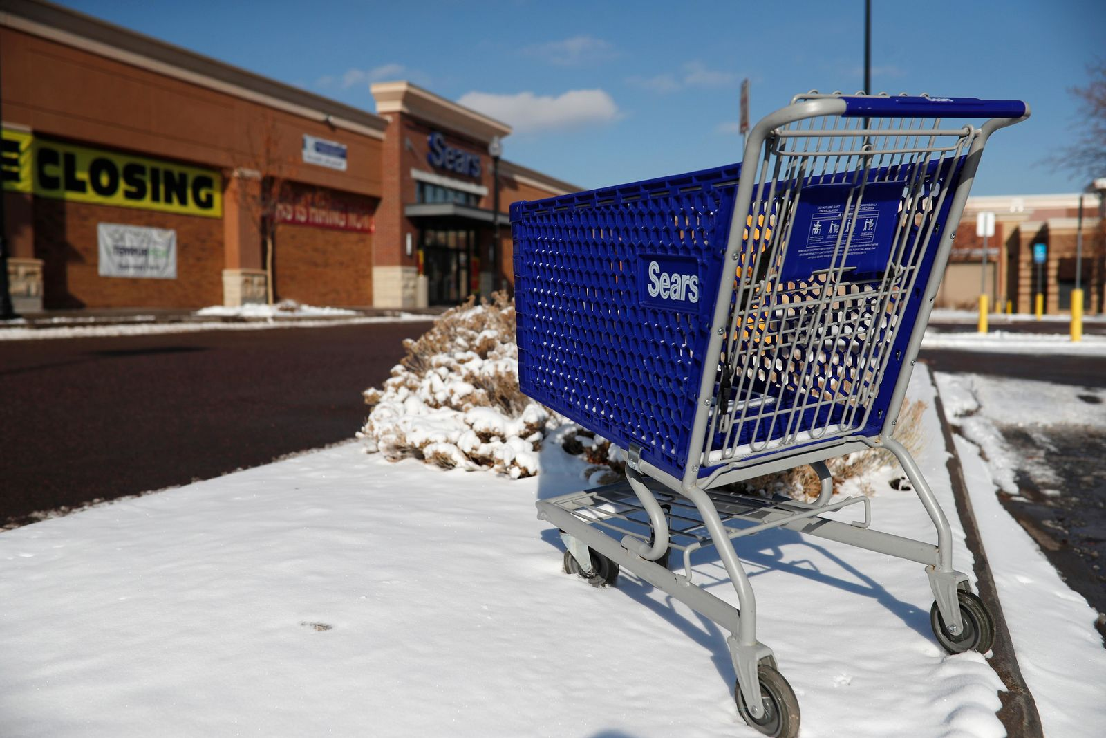 FILE - In this Jan. 1, 2019, file photo, an empty shopping cart sits outside a Sears store in the Streets of Southglenn mall in Littleton, Colo. Nine months out of bankruptcy, Sears is limping into the holiday shopping season. (AP Photo/David Zalubowski, File)