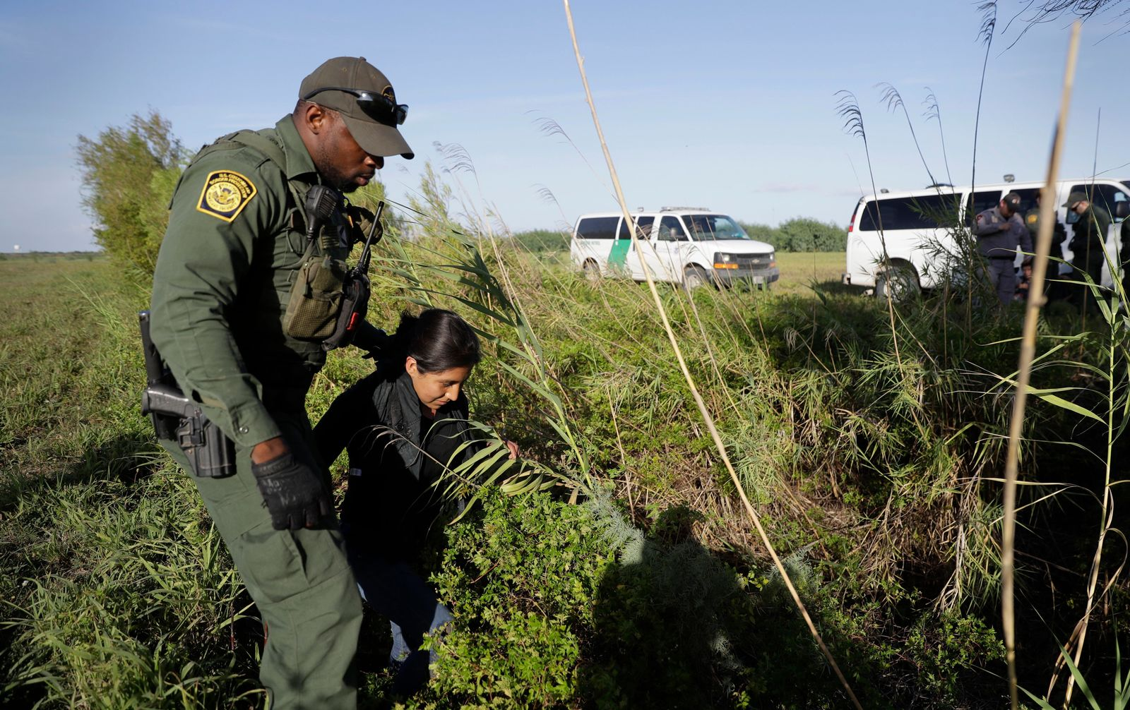 FILE - In this Aug. 11, 2017 file photo a U.S. Customs and Border Patrol agent escorts an immigrant suspected of crossing into the United States illegally along the Rio Grande near Granjeno, Texas. (AP Photo/Eric Gay, File)
