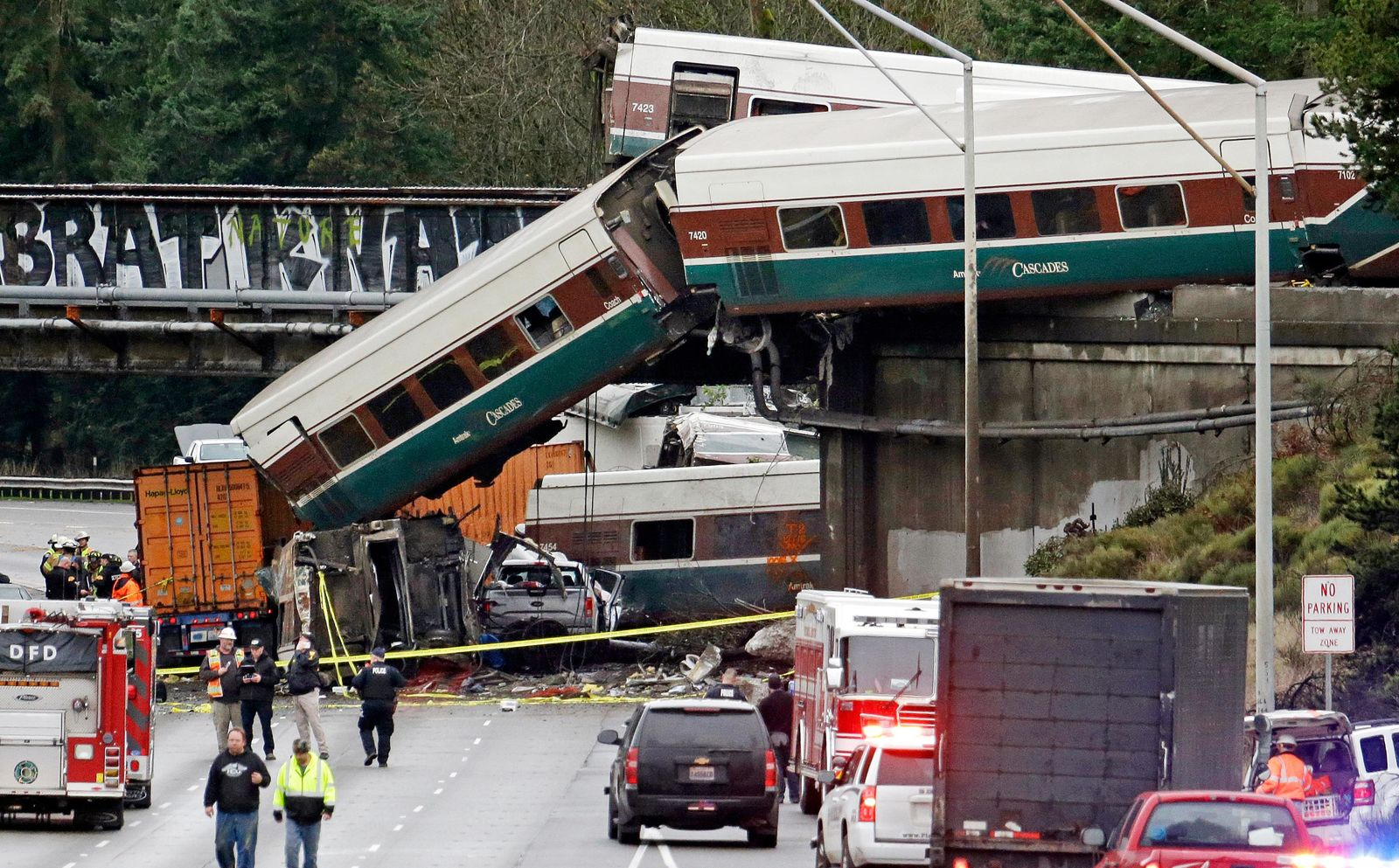FILE - In this Dec. 18, 2017, file photo, cars from an Amtrak train lie spilled onto Interstate 5 below alongside smashed vehicles as some train cars remain on the tracks above in DuPont, Wash. Federal investigators say video aboard the Amtrak train that derailed in Washington state shows crews weren't using personal electronic devices and that the engineer remarked about the speed six seconds before the train went off the tracks south of Seattle. (AP Photo/Elaine Thompson, File)