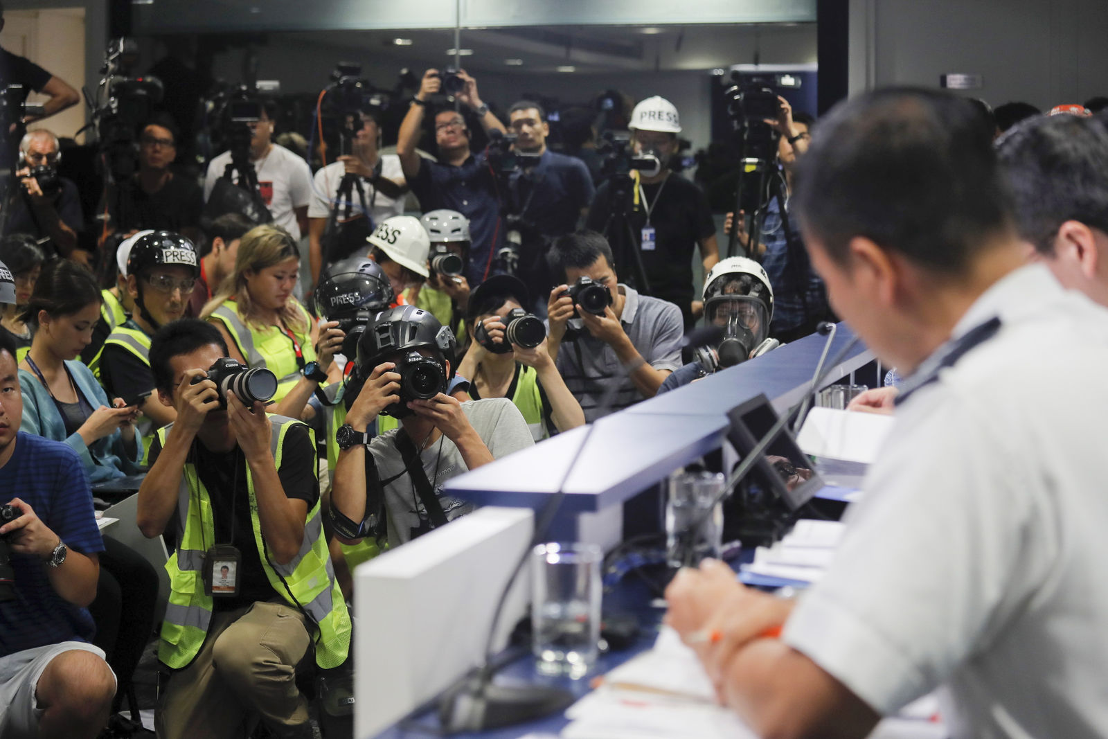 In a sign of protest against the police using force against the media, press photographers wear protective gear during a police media conference in Hong Kong, on Monday, Sept. 9, 2019.. (AP Photo/Kin Cheung)