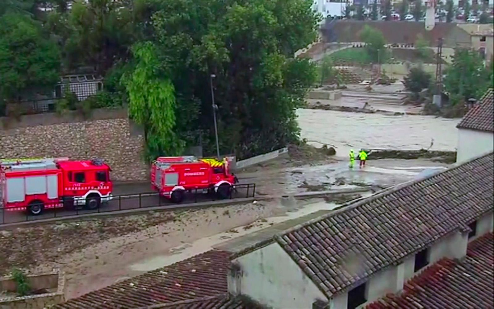 In this image made from video provided by Atlas, fire engines drive by a flooded river, in Ontiyente, Spain, Thursday, Sept. 12 2019.  A large area of southeast Spain was battered Thursday by what was forecast to be its heaviest rainfall in more than a century, with the storms wreaking widespread destruction and killing at least two people. (Atlas via AP)
