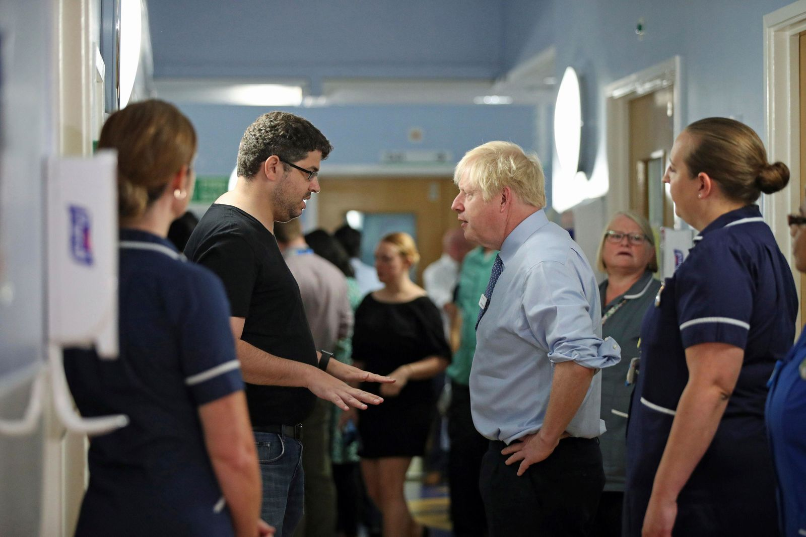 The father of a young patient, who is being treated in the Acorn children's ward, talks to Britain's Prime Minister Boris Johnson during his visit to Whipps Cross University Hospital in Leytonstone, east London, Wednesday Sept. 18, 2019. (Yui Mok/Pool via AP)