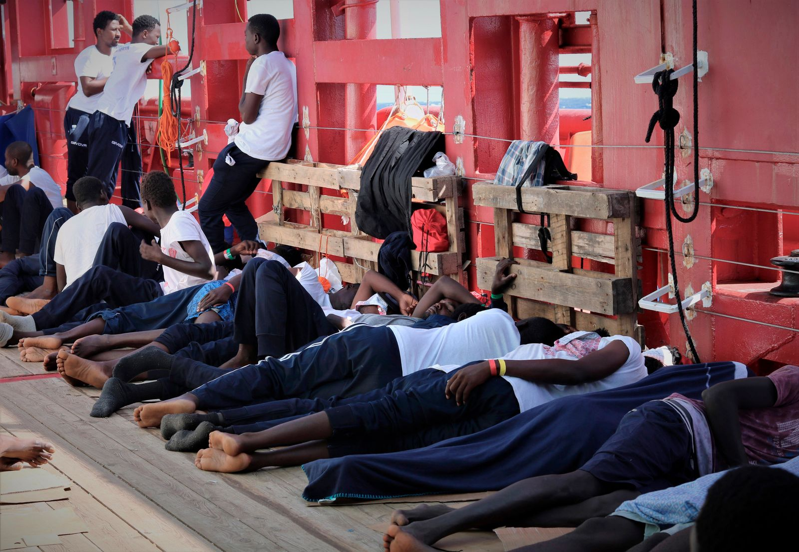 In this Aug. 13, 2019 photo made available Monday, Aug. 19, 2019, rescued migrants rest on the deck of the Norwegian-flagged Ocean Viking vessel, operated by two French humanitarian groups, as it sails in the waters between the Italian island of Linosa, southern Italy, and Malta.{ } (Hannah Wallace Bowman/MSF via AP)