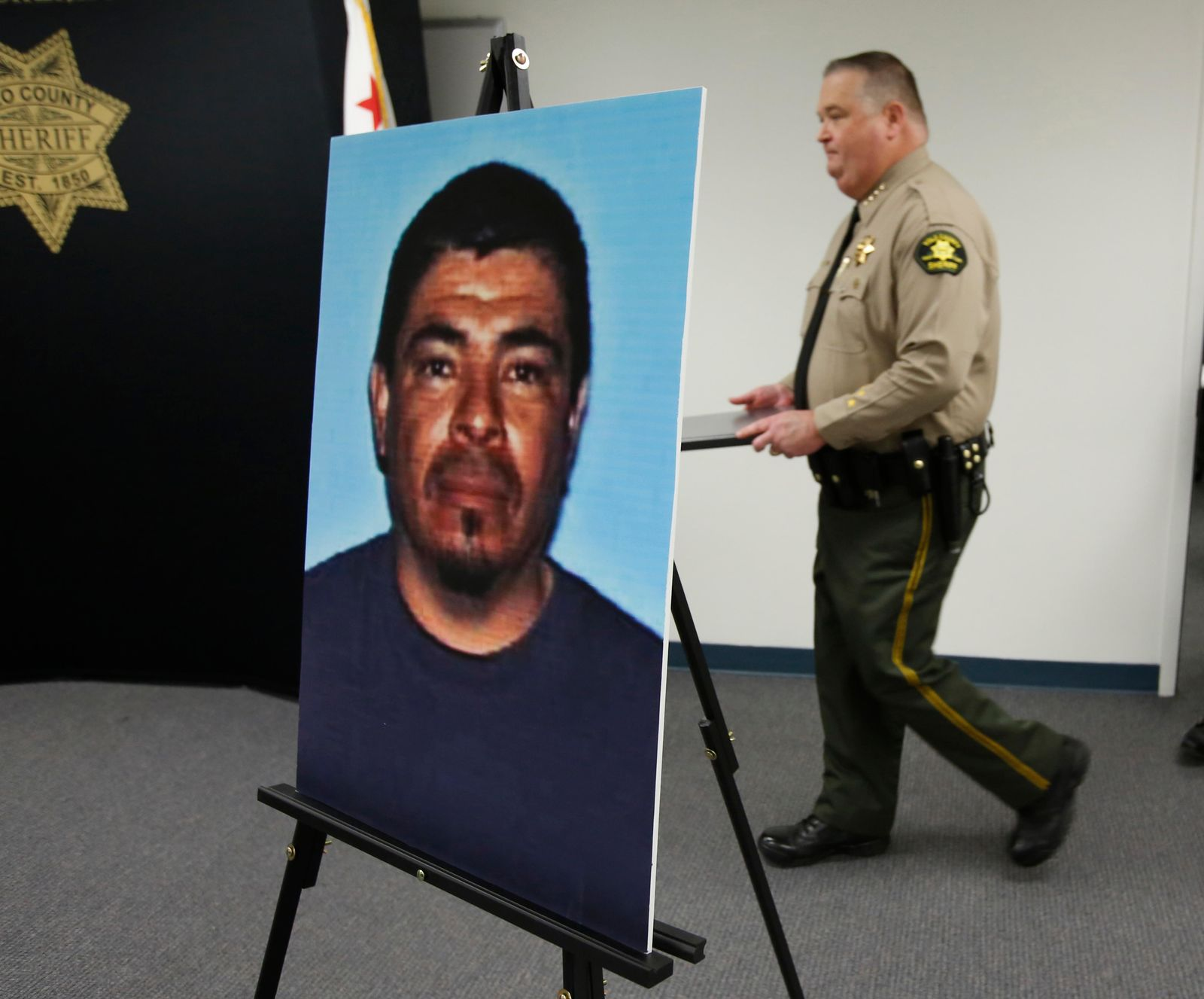 A photo of Paul Perez, who has been arrested in the deaths of his five children, is displayed as Yolo County Sheriff Tom Lopez, right, enters a news conference in Woodland, Calif., Monday, Jan. 27, 2020. Paul Perez, 57, has been arrested in the decades-old killings of five of his infant children, a case the sheriff said had haunted his agency for years, the Yolo County Sheriff's Office said Monday, Jan. 27, 2020. (AP Photo/Rich Pedroncelli)