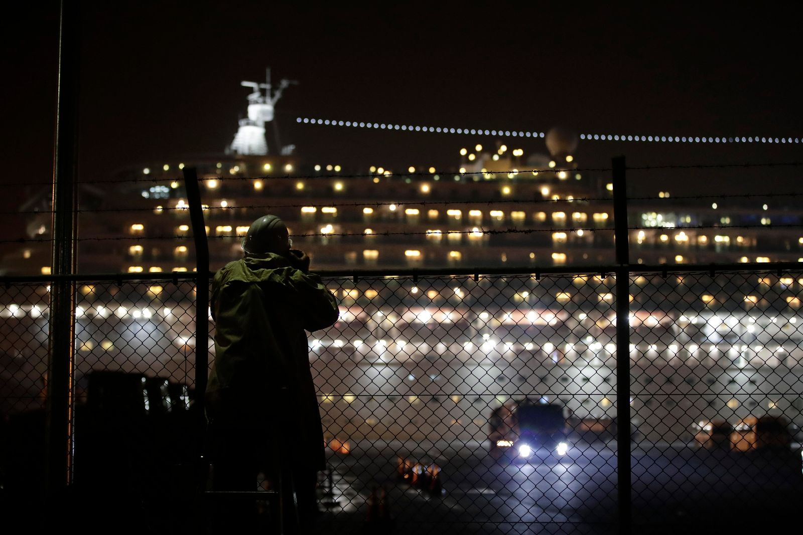 A photographer takes pictures of the quarantined Diamond Princess cruise ship docked at Yokohama Port, near Tokyo, Sunday, Feb. 16, 2020. The U.S. says Americans aboard a quarantined ship will be flown back home on a chartered flight Sunday, but that they will face another two-week quarantine. (AP Photo/Jae C. Hong)