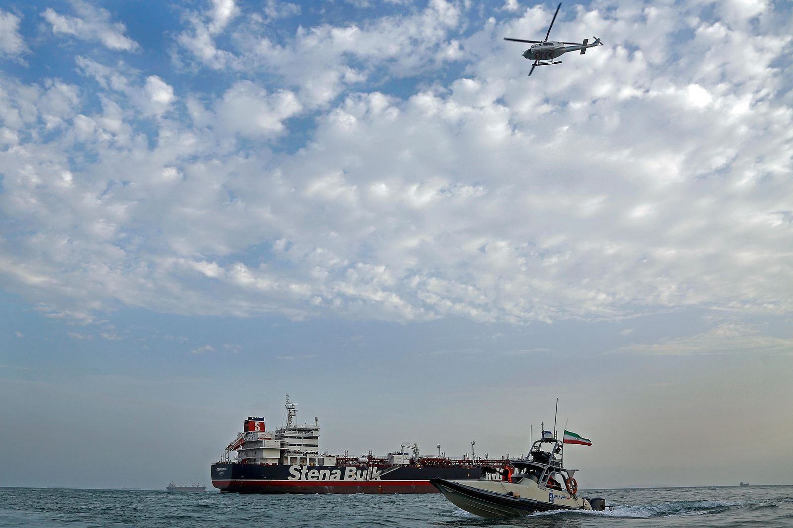 A speedboat and a helicopter of the Iran's Revolutionary Guard move around a British-flagged oil tanker Stena Impero which was seized on Friday by the Guard, in the Iranian port of Bandar Abbas, Sunday, July 21, 2019. (Hasan Shirvani/Mizan News Agency via AP)