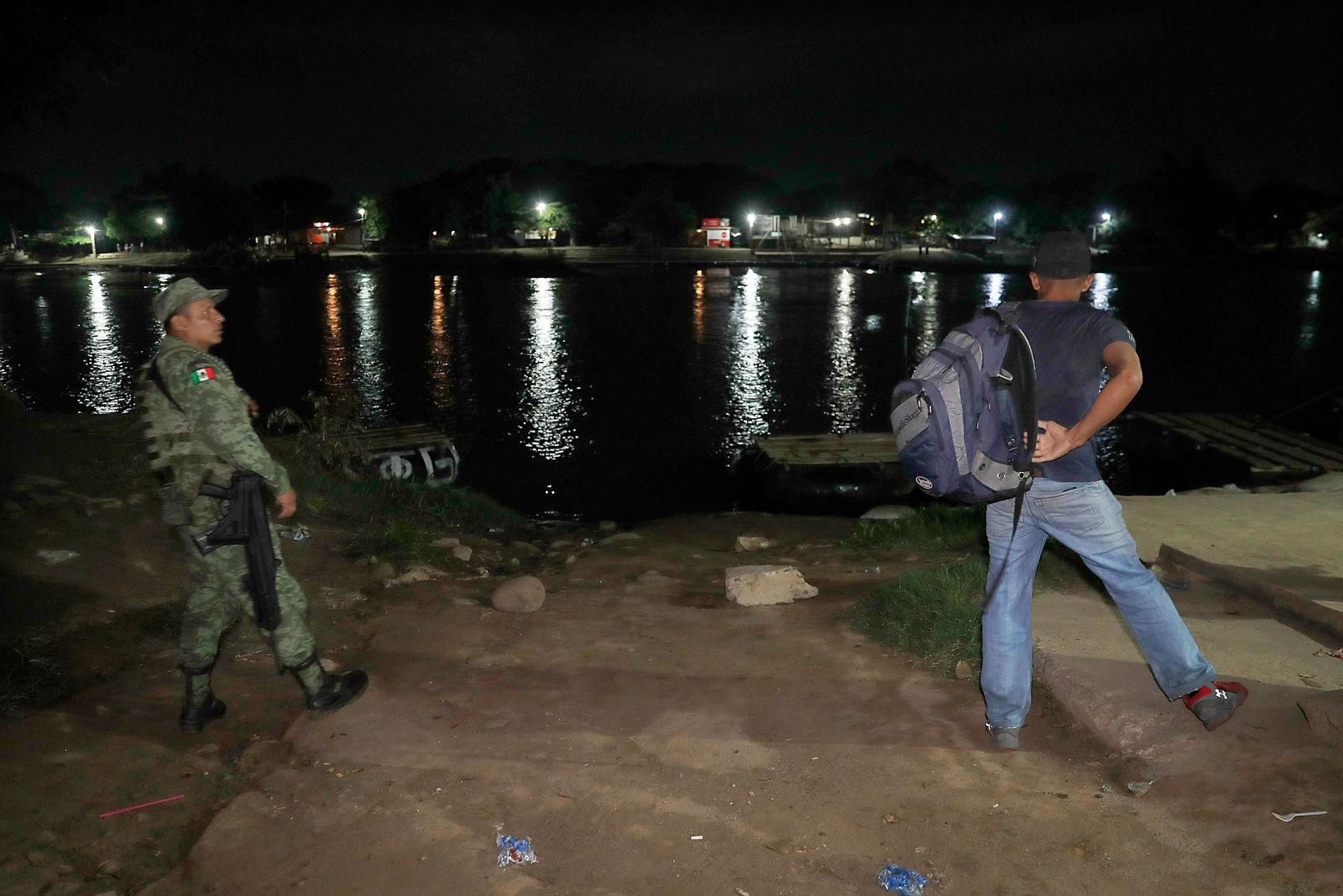 A soldier briefly questions a Honduran migrant who just crossed the Suchiate River, Mexico's natural border with Guatemala, before allowing him to go near Ciudad Hidalgo, Mexico, early Sunday, June 9, 2019. (AP Photo/Marco Ugarte)