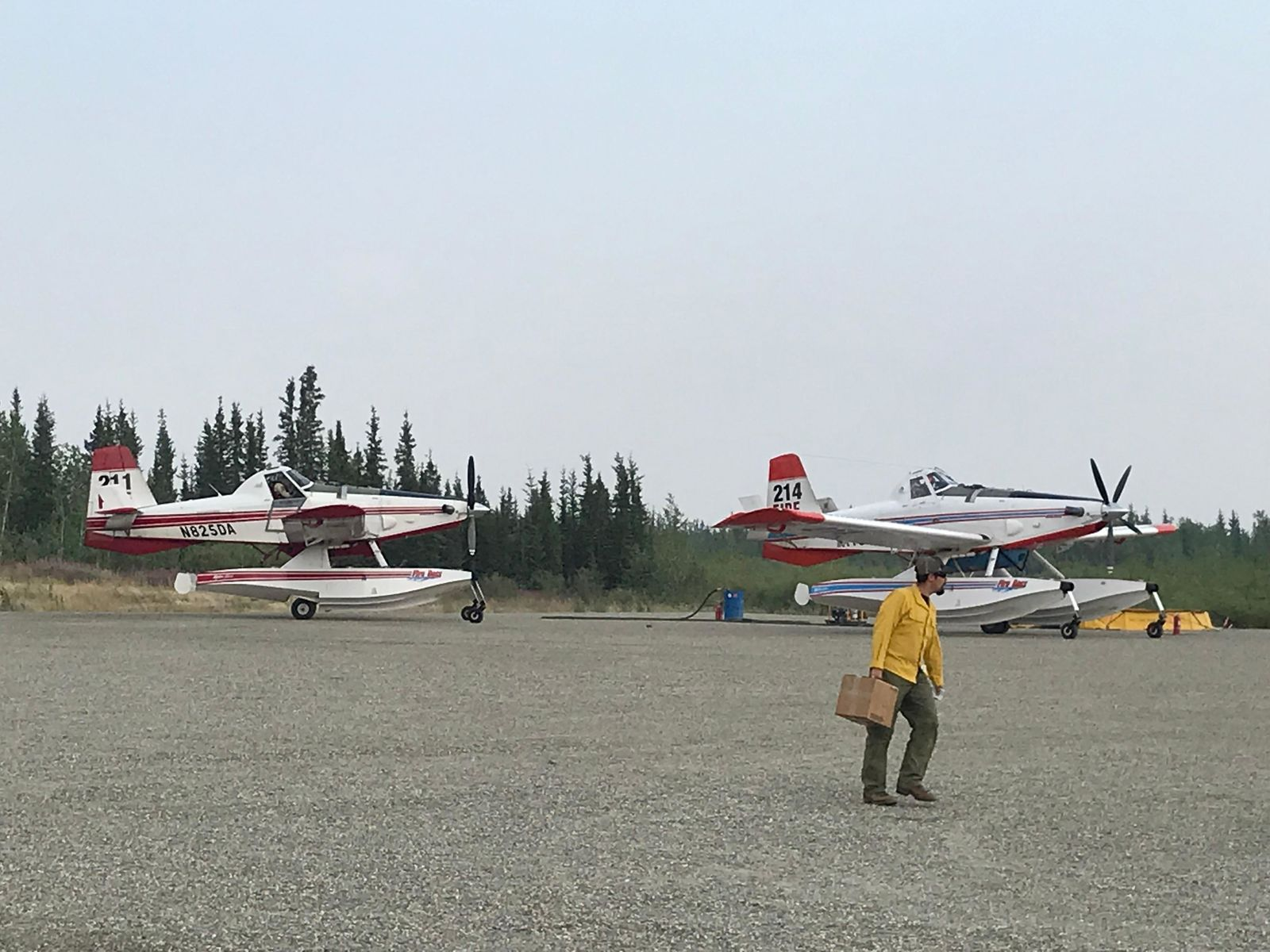 A firefighter walks in front of planes parked on a gravel lot (Couresty Medford Crew 10){ }