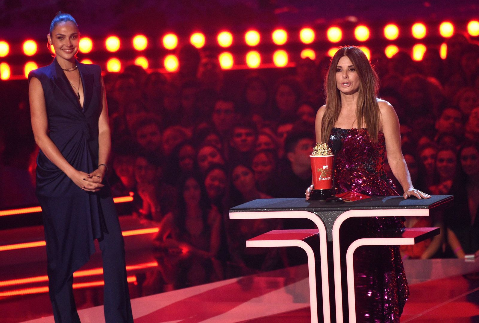"Sandra Bullock accepts the award for most frightened performance for ""Bird Box"" as presenter Gal Gadox looks on at the MTV Movie and TV Awards on Saturday, June 15, 2019, at the Barker Hangar in Santa Monica, Calif. (Photo by Chris Pizzello/Invision/AP)"