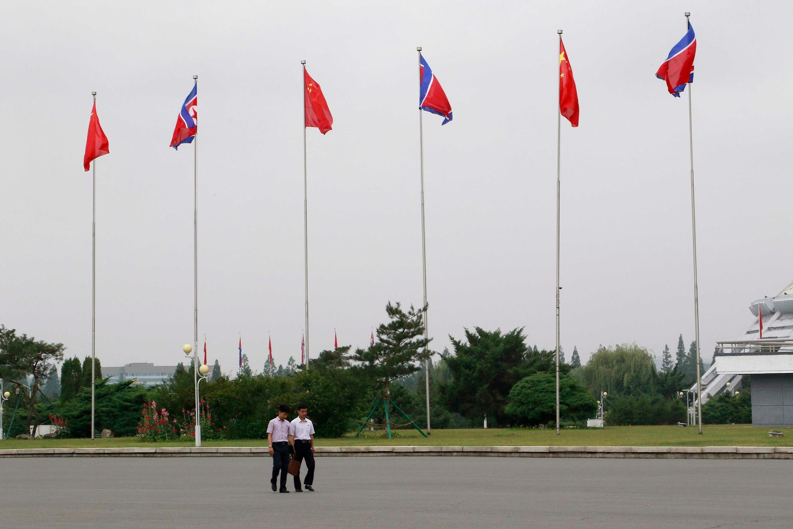 North Korean walk on a street where North Korean and Chinese national flags are hoisted in Pyongyang, North Korea Thursday, June 20, 2019.{ } (AP Photo/Cha Song Ho)