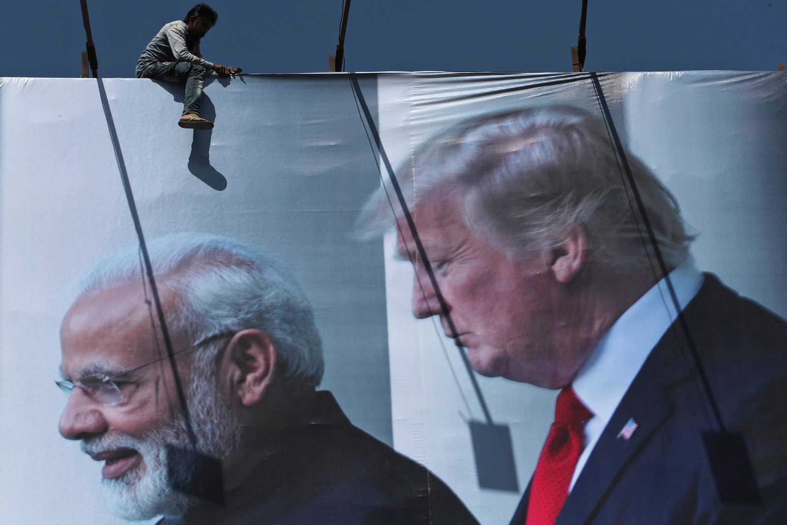 An Indian worker installs a giant hoarding welcoming U.S. President Donald Trump ahead of his visit, in Ahmadabad, India, Thursday, Feb. 20, 2020. Trump is scheduled to visit the city during his Feb. 24-25 India trip. (AP Photo/Ajit Solanki)