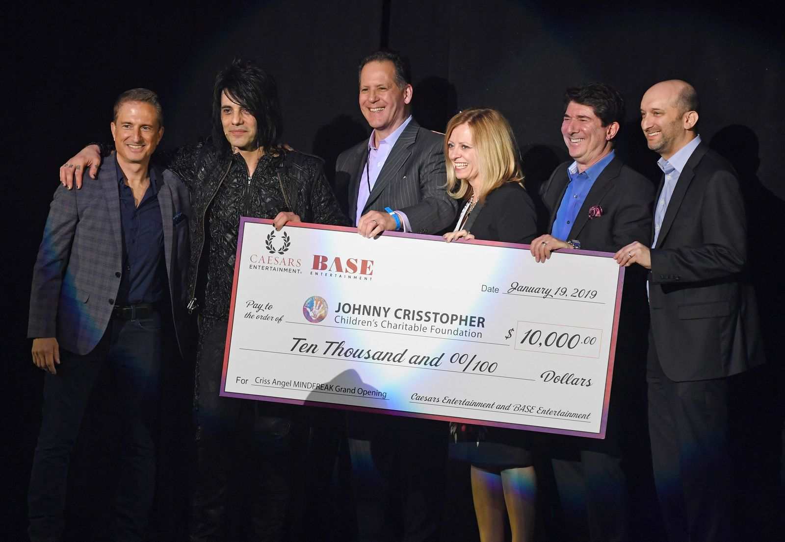 "LAS VEGAS, NEVADA - JANUARY 19:  (L-R) LBI Entertainment Co-Founder Dave Baram, illusionist Criss Angel, BASE Entertainment Chief Operating Officer Mark Maluso, Planet Hollywood Resort & Casino General Manager Sherri Pucci Sosa, BASE Entertainment CEO Brian Becker and Caesars Entertainment Senior Vice President of Entertainment Jason Gastwirth pose onstage after Caesars Entertainment and BASE Entertainment presented Angel with a USD 10,000 check for his Johnny Crisstopher Children's Charitable Foundation  the grand opening of ""Criss Angel MINDFREAK"" at Planet Hollywood Resort & Casino on January 19, 2019 in Las Vegas, Nevada.  (Photo by Ethan Miller/Getty Images for Planet Hollywood Resort & Casino)"