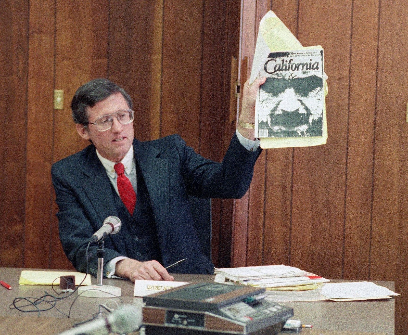 FILE - In this Feb. 9, 1989 file photo, Los Angeles Deputy District Attorney Stephen Kay holds up a magazine profiling convicted murderer Charles Manson while delivering his closing statement at Manson's parole hearing at San Quentin Prison, Calif.{ } (AP Photo/Eric Risberg, File)