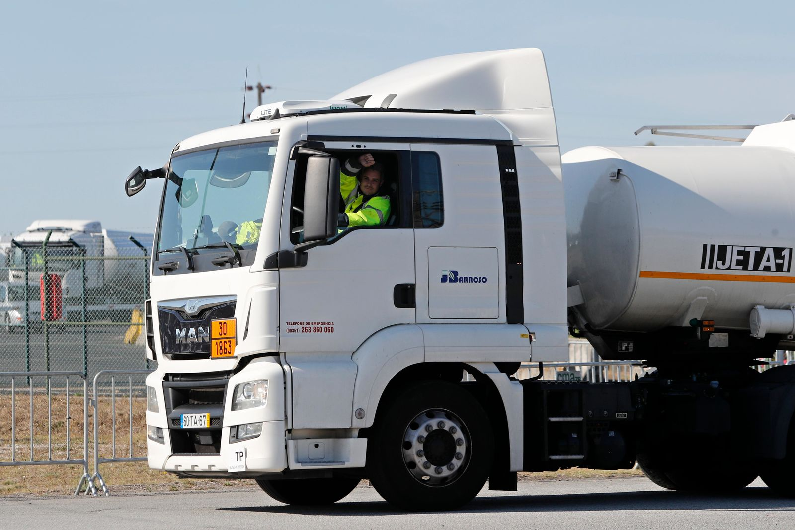 The driver of a jet fuel truck gestures to cheering truck drivers standing outside a fuel depot in Aveiras, outside Lisbon, Monday, Aug. 12, 2019.{ } gallons) for customers at gas stations until further notice. (AP Photo/Armando Franca)