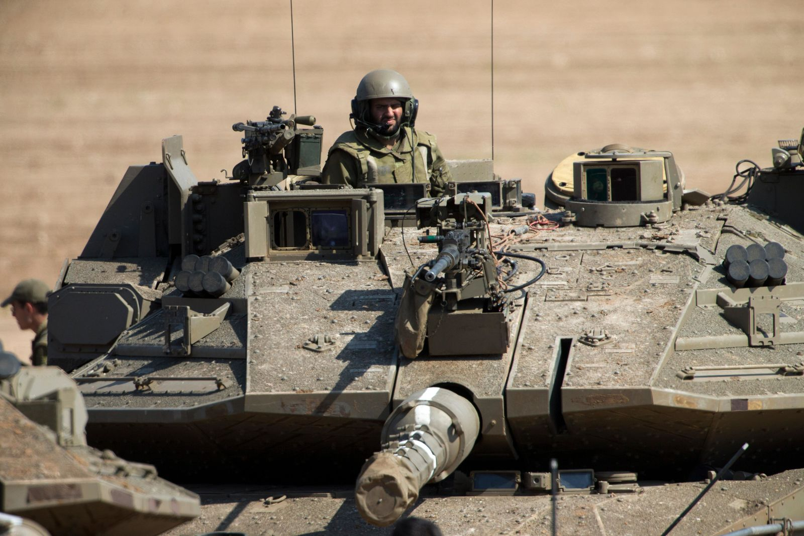 An Israeli soldier drives a tank at a gathering area near the Israel-Gaza border, in southern Israel, Tuesday, March 26, 2019.{ } (AP Photo/Ariel Schalit)