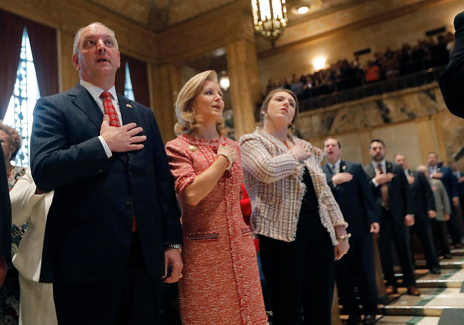 FILE - In this  Monday, April 8, 2019 file photo, Louisiana Gov. John Bel Edwards holds his hand to his heart with his wife, Donna Edwards, and their daughter Sarah Ellen Edwards, right, during the pledge of allegiance at the opening of the annual state legislative session in Baton Rouge, La. (AP Photo/Gerald Herbert, Pool, File)