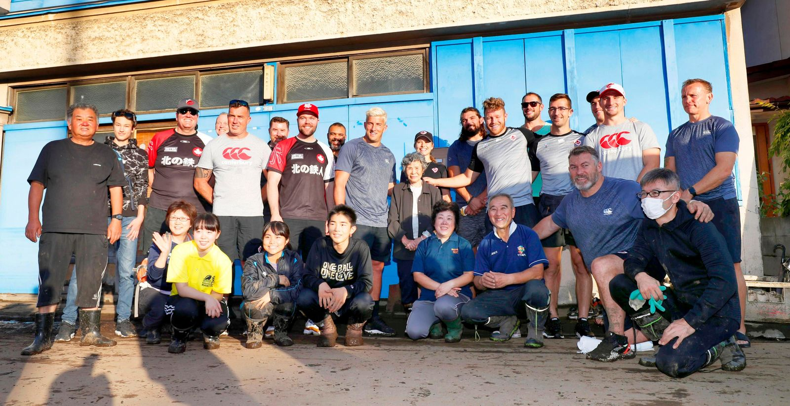 In this Oct. 13, 2019, photo, Canadian rugby team players pose with residents after their volunteer activity in Kamaishi, Iwate prefecture,  Japan, following the cancellation of their Rugby World Cup Pool B match against Namibia due to Typhoon Hagibis. r. (Kyodo News via AP)