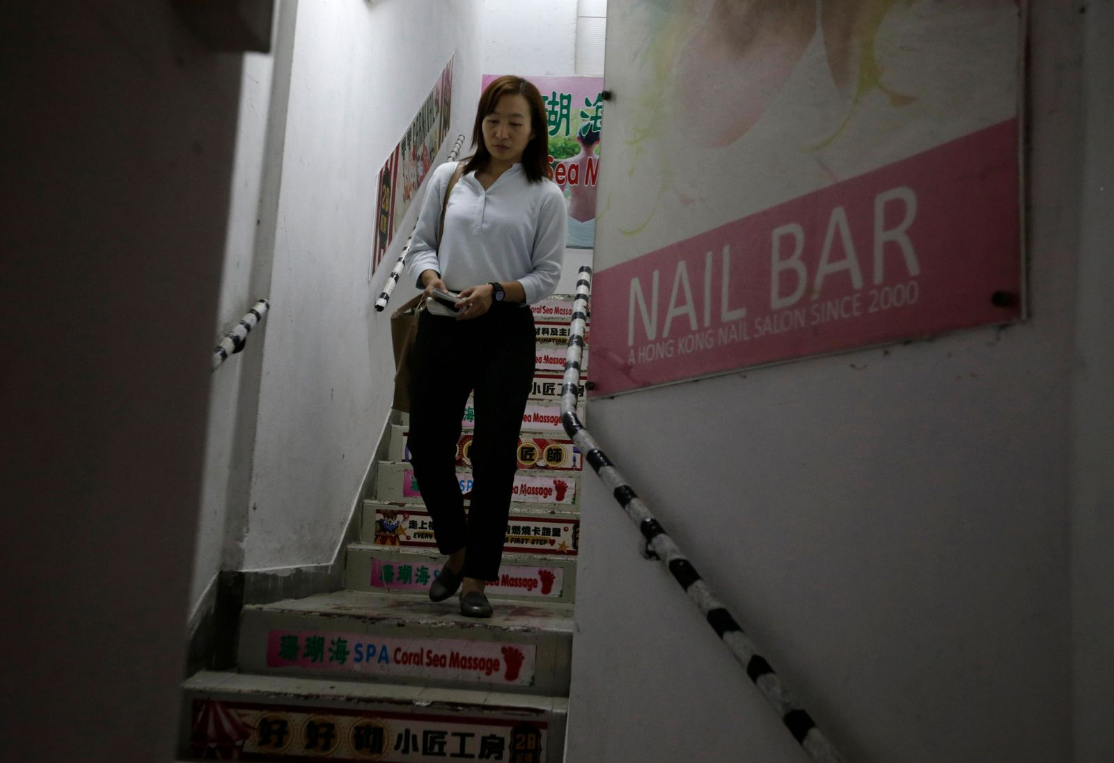 In this photo taken Thursday, Nov. 7, 2019, district council candidate Cathy Yau walks down the stairs of a building during a door-to-door campaign at Causeway Bay in Hong Kong.{ } (AP Photo/Dita Alangkara)