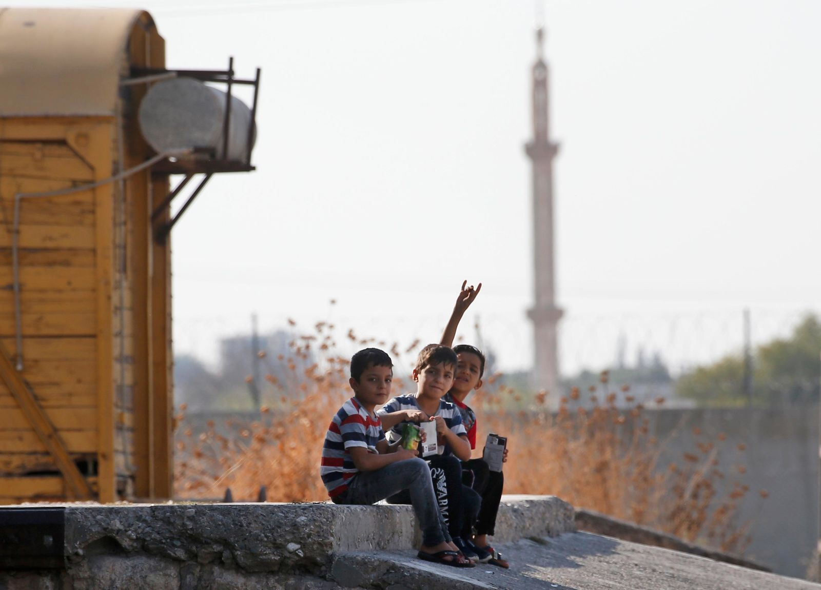 Children gesture to the camera in Akcakale Sanliurfa province, southeastern Turkey, at the border with Syria, Friday, Oct. 18, 2019. (AP Photo/Lefteris Pitarakis)