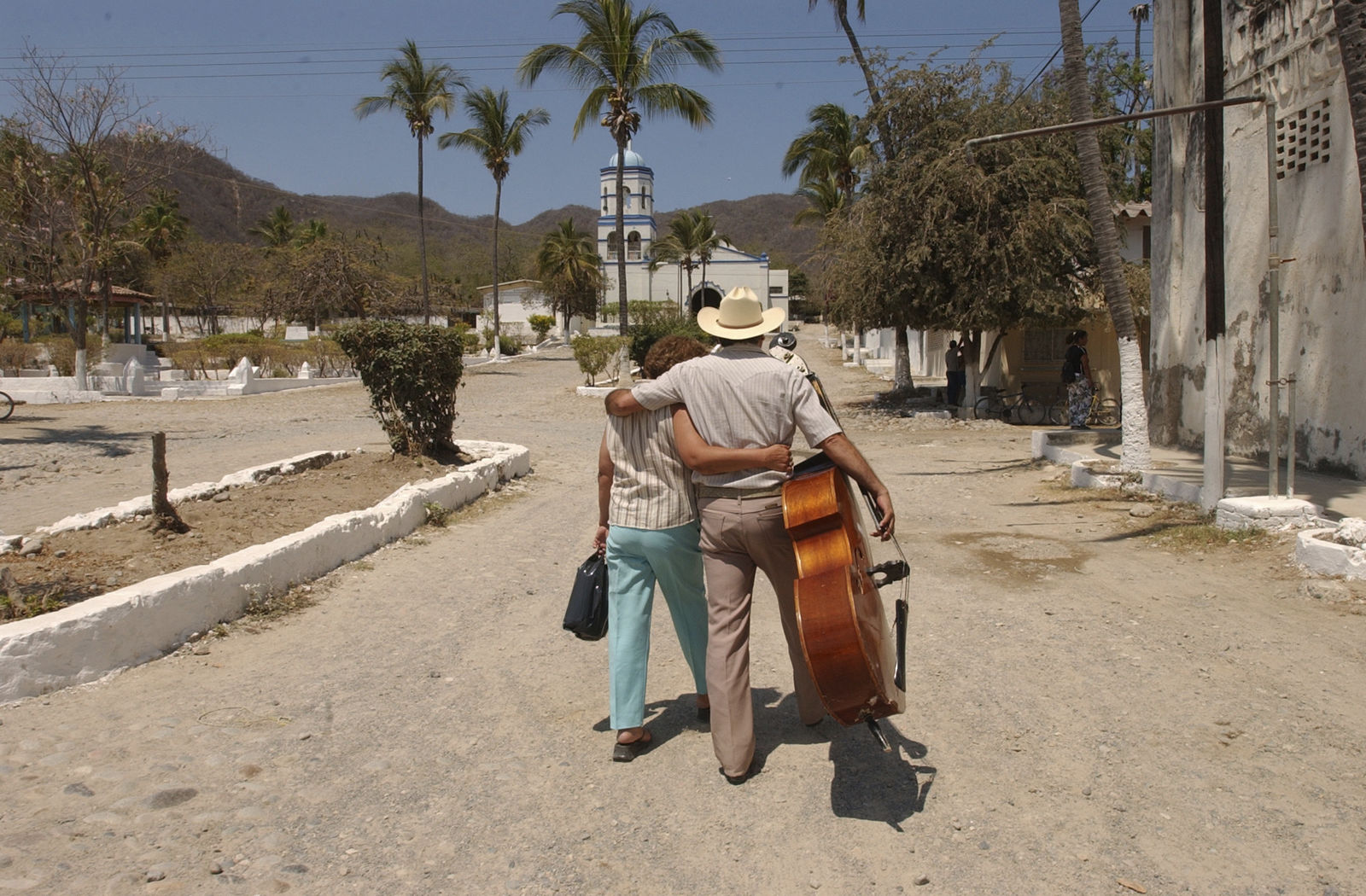 FILE - In this May 12, 2005 file photo, inmate Francisco Loera, who is serving a 10 year sentence, walks with his bass while embracing his partner Alicia Anchondo who arrived to visit him at the Islas Marias federal prison island, located 90 miles south of Mazatlan, Mexico. (AP Photo/Eduardo Verdugo, File)