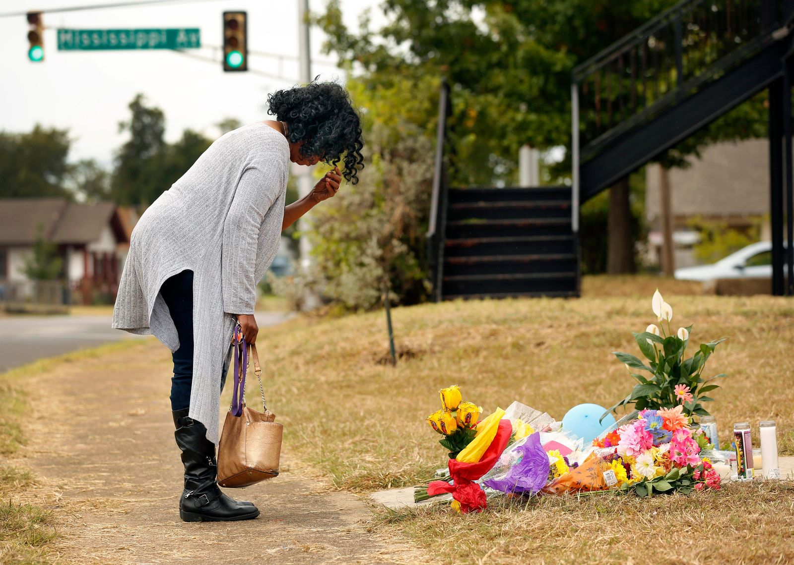 Lynda Menefee, of Fort Worth, makes the sign of the cross after leaving flowers on the front sidewalk of Atatiana Jefferson's home on E. Allen Ave in Fort Worth, Texas, Tuesday, Oct. 15, 2019. (Tom Fox/The Dallas Morning News via AP)