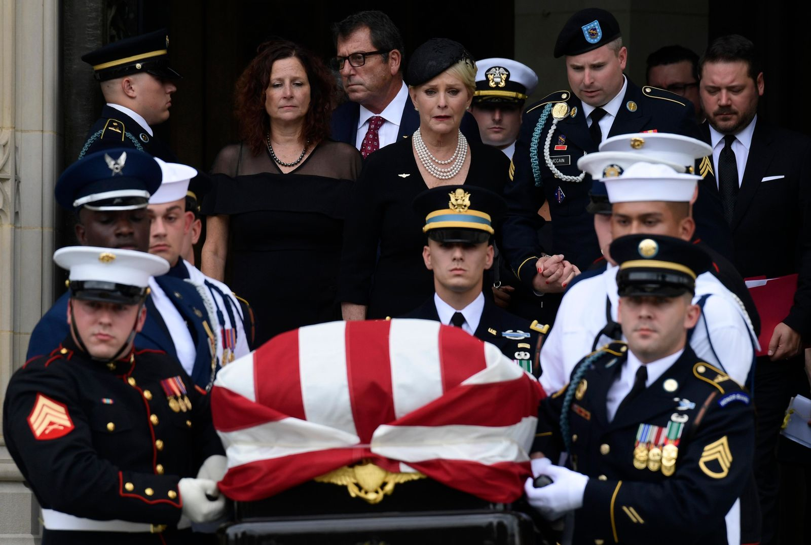 Cindy McCain, center, widow of Sen. John McCain, R-Ariz., escorted by her son Jimmy McCain and other family members, follows his casket as it is carried out of Washington National Cathedral in Washington, Saturday, Sept. 1, 2018, following a memorial service. (AP Photo/Susan Walsh)