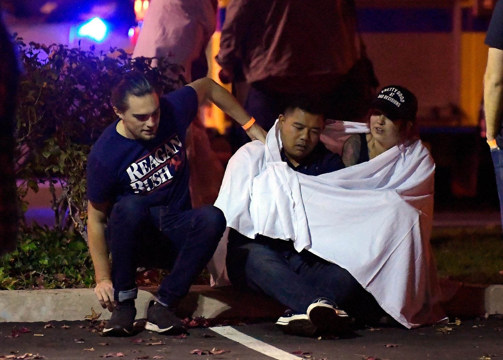 "People comfort each other as they sit near the scene Thursday, Nov. 8, 2018, in Thousand Oaks, Calif. where a gunman opened fire Wednesday inside a country dance bar crowded with hundreds of people on ""college night."" (AP Photo/Mark J. Terrill)"