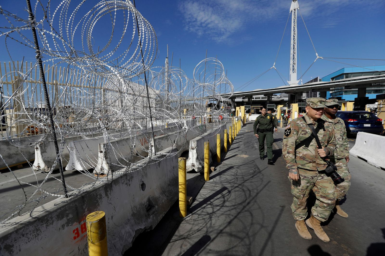 U.S. Border Patrol agents and members of the military pass concertina wire during a tour of the San Ysidro port of entry Friday, Nov. 16, 2018, in San Diego. As thousands of migrants in a caravan of Central American asylum-seekers converge on the doorstep of the United States, what they won't find are armed American soldiers standing guard. Instead they will see cranes installing towering panels of metal bars and troops wrapping concertina wire around barriers while military helicopters fly overhead. (AP Photo/Gregory Bull)