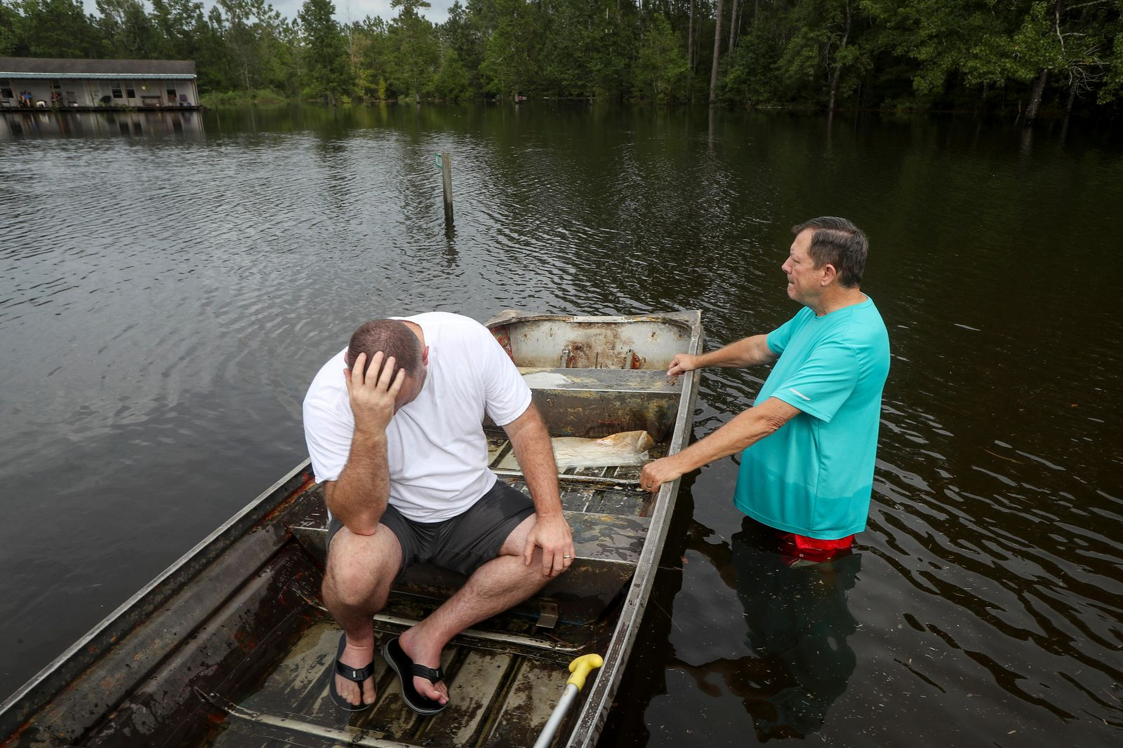 "Stephen Gilbert, left, and his father-in-law sit in front of their flooded property on Friday, Sept. 20, 2019, in the Mauriceville, Texas, area. Floodwaters are starting to recede in most of the Houston area after the remnants of Tropical Storm Imelda flooded parts of Texas. ""I'm on my third house,"" said Gilbert, who lives behind his father-in-law. ""I wouldn't go anywhere else in the world,"" he said. ""All we have is family anyway."" ( Jon Shapley/Houston Chronicle via AP)"