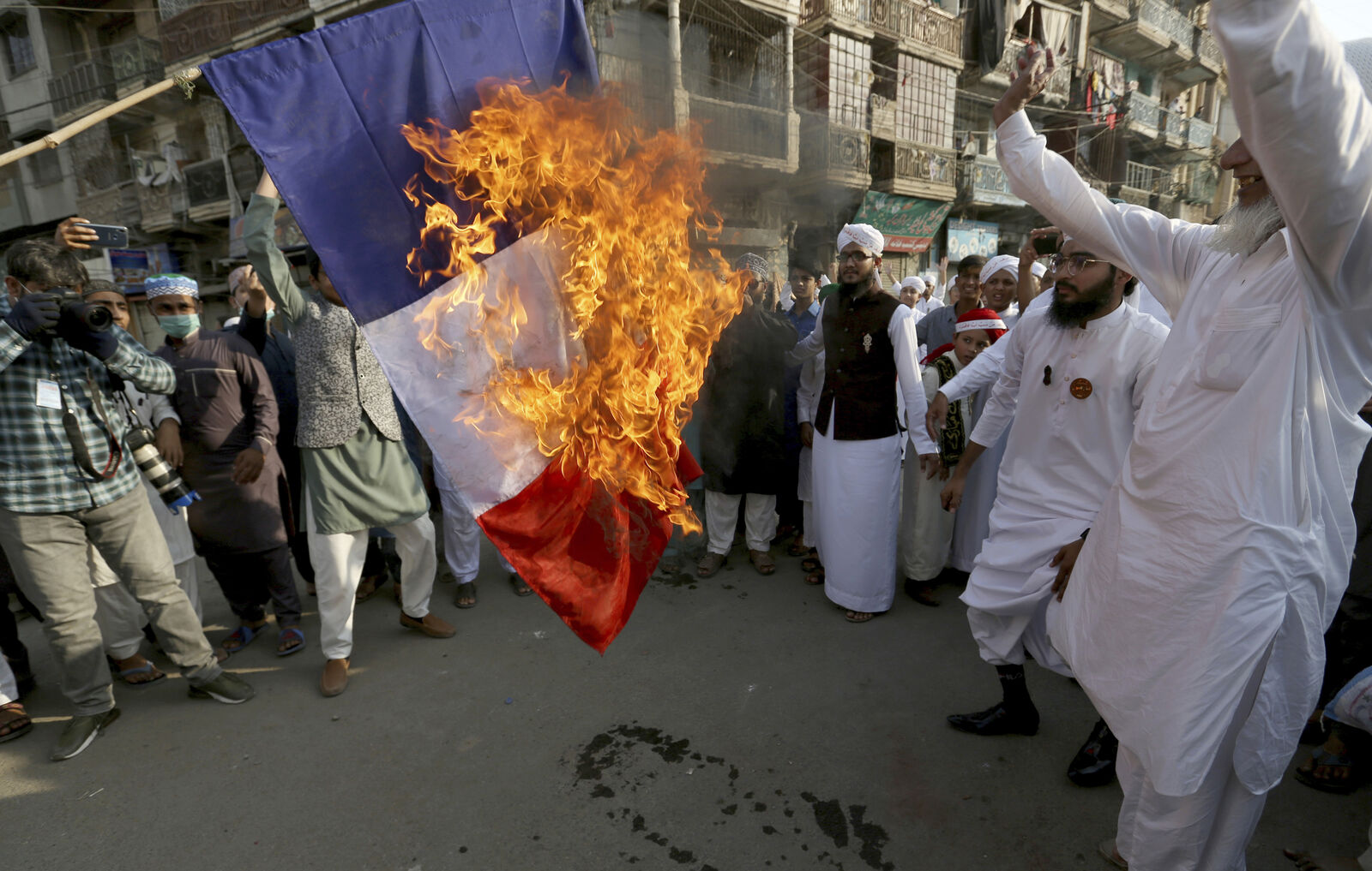 Supporters of religious group burn a representation of a French flag during a rally against French President Emmanuel Macron and republishing of caricatures of the Prophet Muhammad they deem blasphemous, in Karachi, Pakistan, Friday, Oct. 30, 2020.{ } (AP Photo/Fareed Khan)