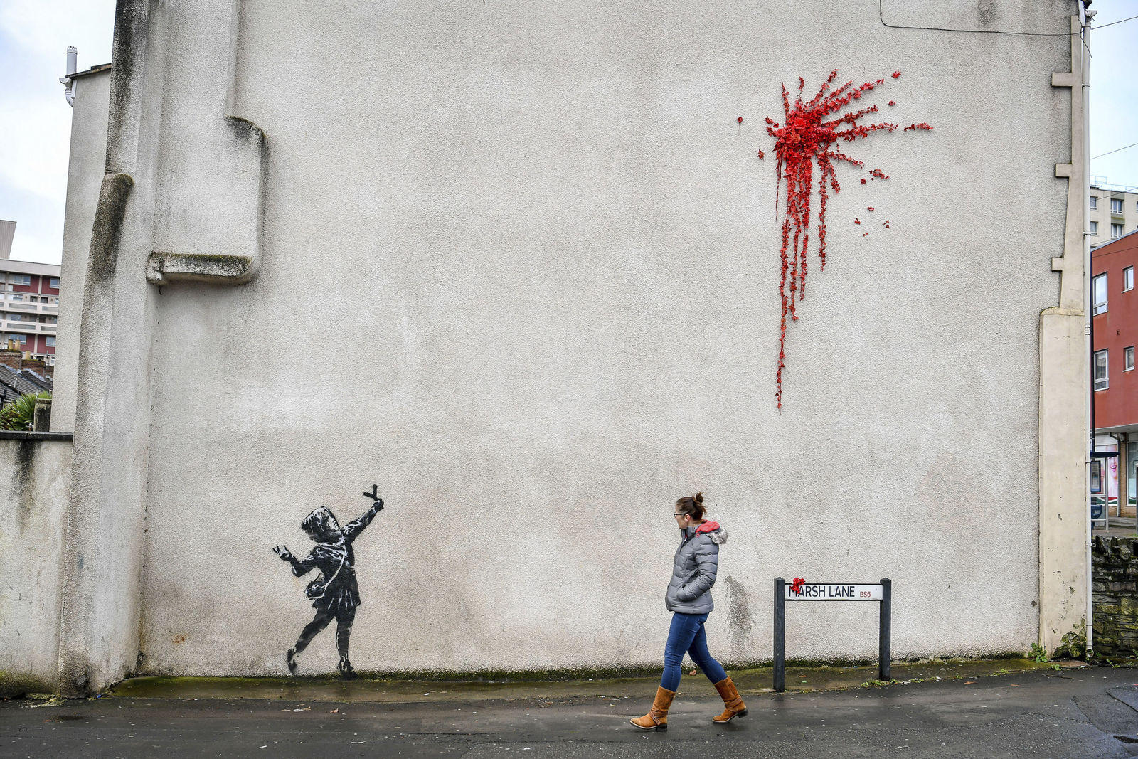A woman walks past a new artwork on the side of a house in Bristol, England, Thursday Feb. 13, 2020, which has been confirmed as the work of street artist Banksy. (Ben Birchall/PA via AP)