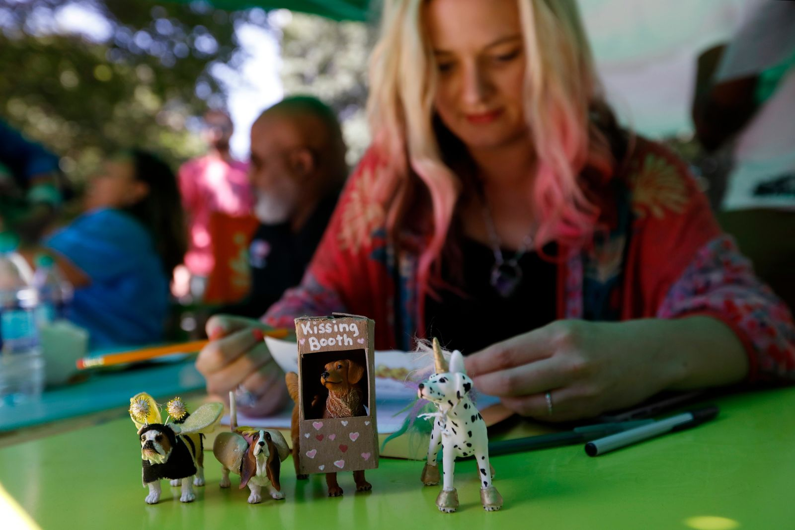 Karen Anderson Singer, a Doggy Con costume contest judge, reviews her notes before announcing the Tiny Doors Award winner, Saturday, Aug. 17, 2019, in Atlanta. Singer, an artist for the Atlanta-based community project Tiny Doors ATL, unveiled a Tiny Door installment in Woodruff Park after Doggy Con. (AP Photo/Andrea Smith)