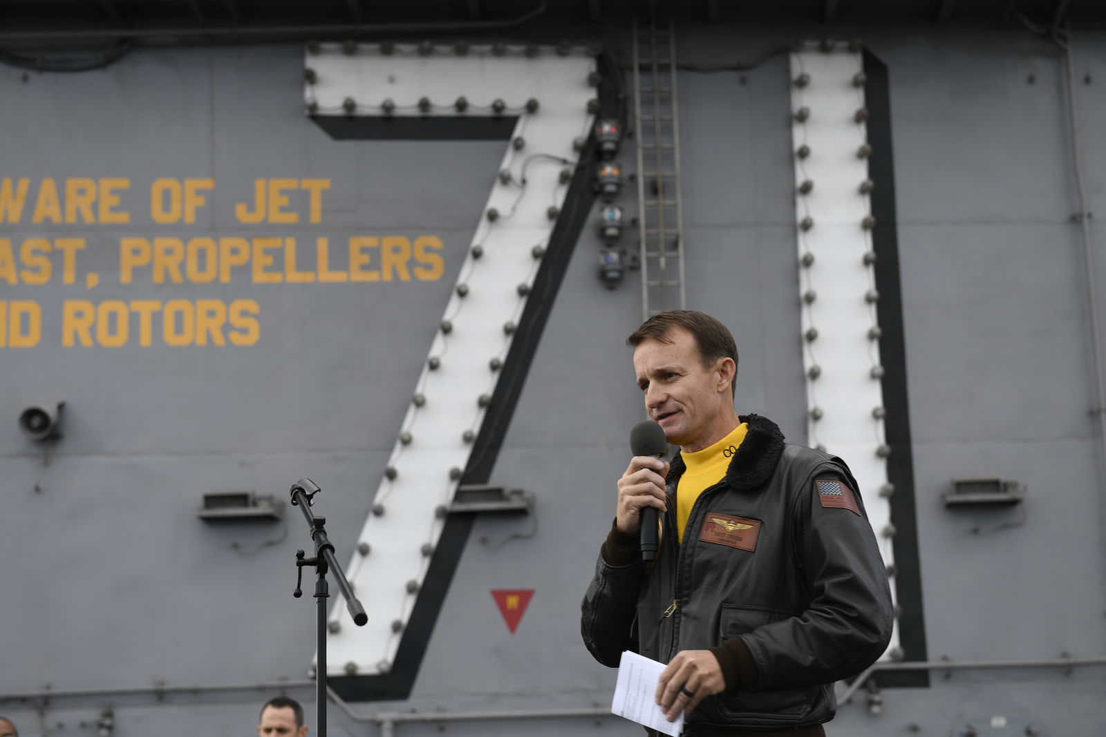 In this Nov. 15, 2029, photo U.S. Navy Capt. Brett Crozier, commanding officer of the aircraft carrier USS Theodore Roosevelt (CVN 71), addresses the crew during an all-hands call on the ship's flight deck while conducting routine operations in the Eastern Pacific Ocean. (U.S. Navy Photo by Mass Communication Specialist 3rd Class Nicholas Huynh via AP)