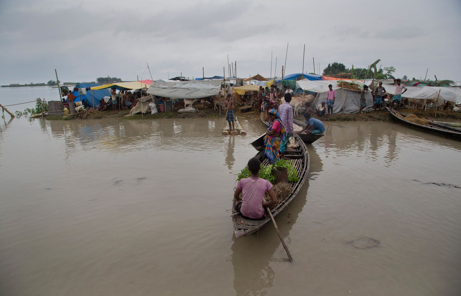 Flood affected villagers travel on a boat as others take shelter on a highland in Katahguri village along the river Brahmaputra, east of Gauhati, India, Sunday, July 14, 2019. Officials in northeastern India said more than a dozen people were killed and over a million affected by flooding. Rain-triggered floods, mudslides and lightning have left a trail of destruction in other parts of South Asia. (AP Photo/Anupam Nath)
