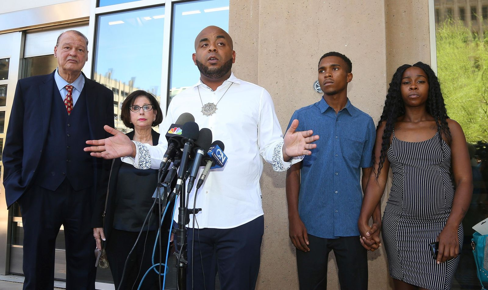 Rev. Jarrett Maupin, center, a civil rights advocate, speaks during a news conference as Dravon Ames, second from right, and Iesha Harper, right, are joined by their attorneys Sandra Slaton, second from left, and Tom Horne, left, at Phoenix City Hall, Monday, June 17, 2019, in Phoenix. (AP Photo/Ross D. Franklin)