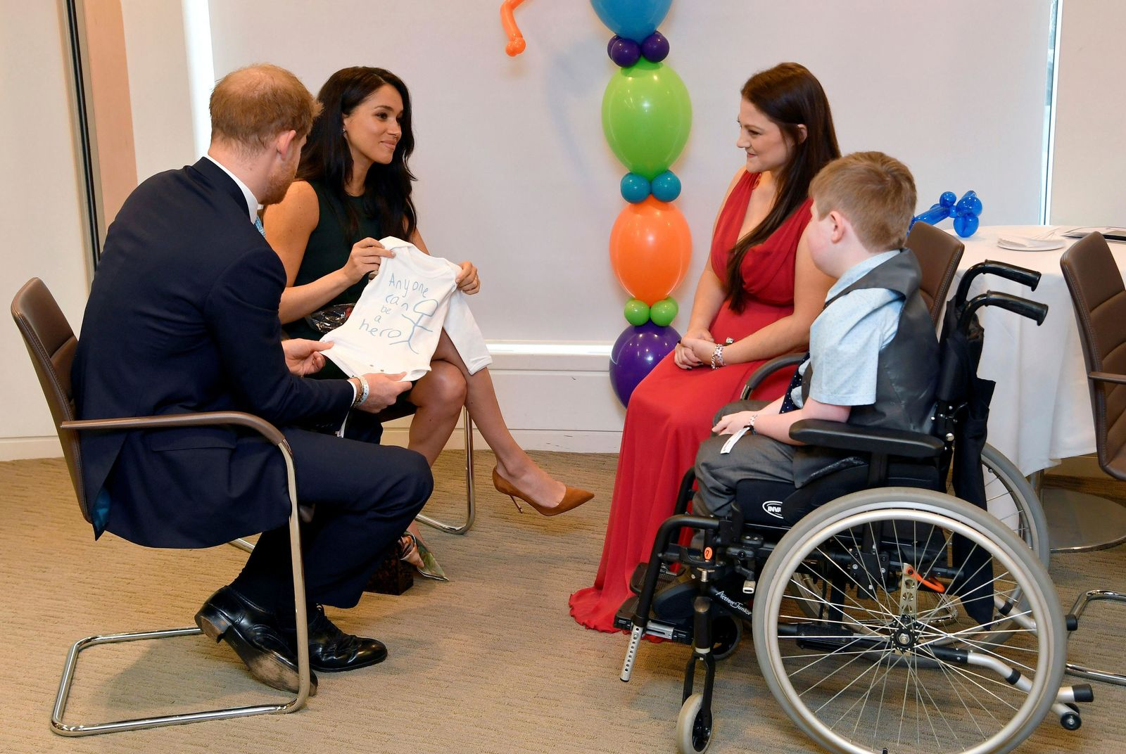 Britain's Prince Harry and Duchess of Sussex, left, look at a t-shirt designed by William Mgee and mother Kelly during the annual WellChild Awards in London, Tuesday Oct. 15, 201. (Toby Melville/Pool via AP)