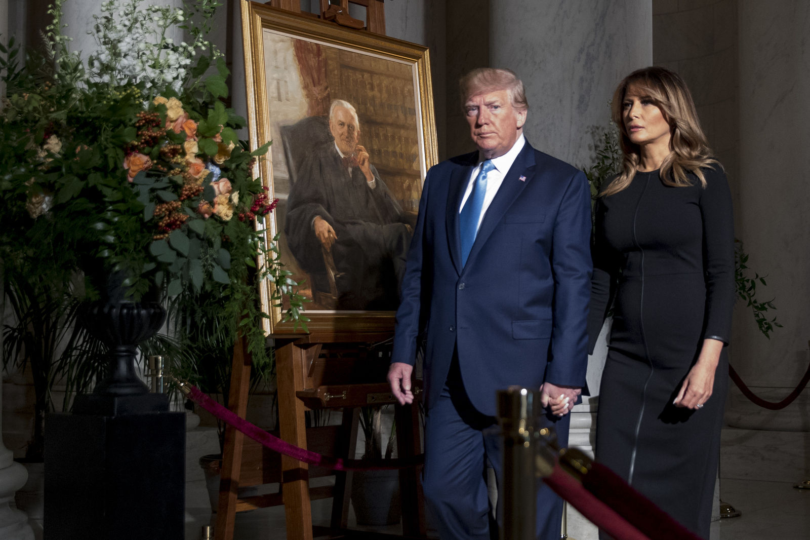 President Donald Trump and first lady Melania Trump walk past a painting of the late Supreme Court Justice John Paul Stevens after they pay their respects as he lies in repose in the Great Hall of the Supreme Court in Washington, Monday, July 22, 2019. (AP Photo/Andrew Harnik, pool)
