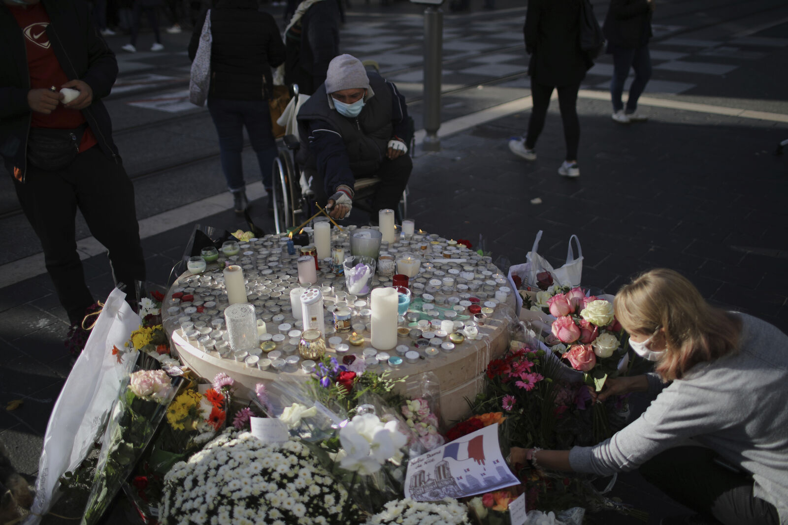 people set flowers, messages and candles in front of the Notre Dame church, in Nice, France, Friday, Oct. 30, 2020. (AP Photo/Daniel Cole)