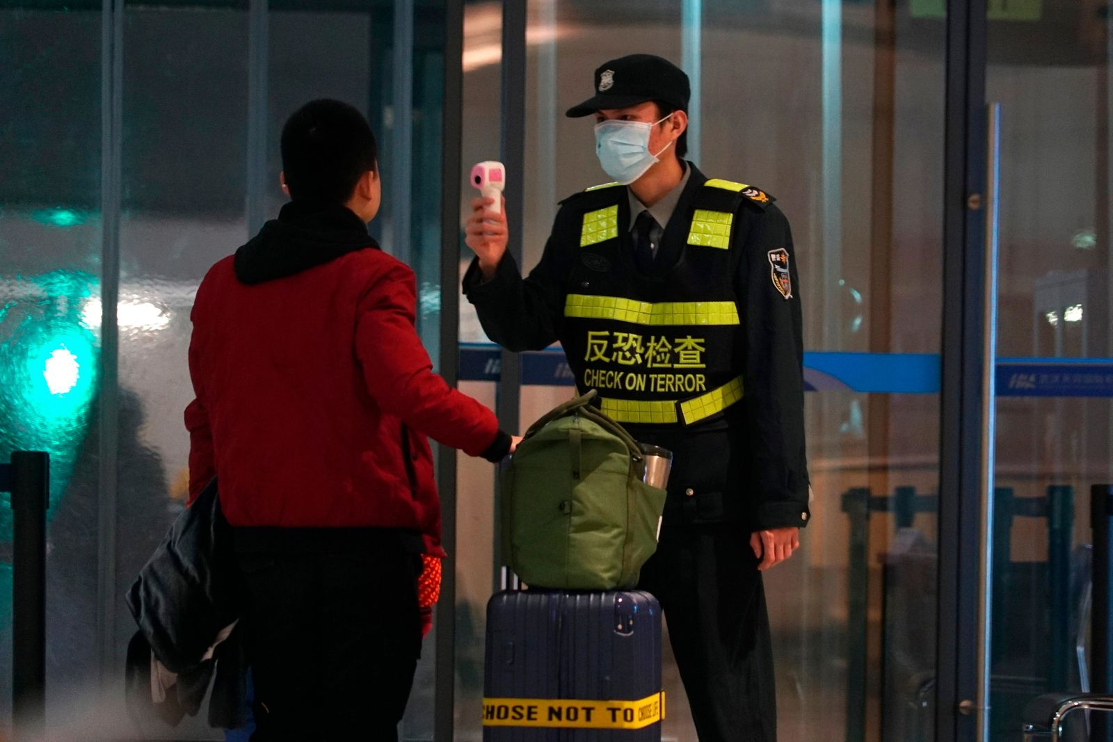 An airport staff member uses a temperature gun to check people leaving Wuhan Tianhe International Airport in Wuhan, China, Tuesday, Jan. 21, 2020. Heightened precautions were being taken in China and elsewhere Tuesday as governments strove to control the outbreak of a novel coronavirus that threatens to grow during the Lunar New Year travel rush. (AP Photo/Dake Kang)
