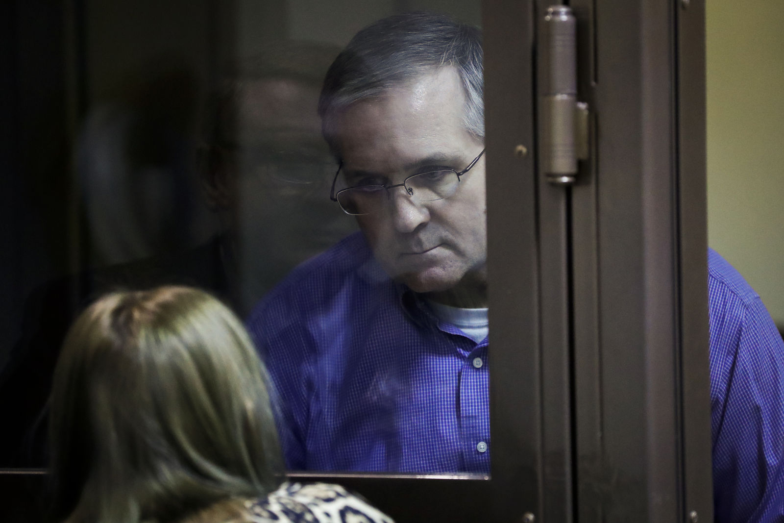 Paul Whelan, a former U.S. Marine, who was arrested in Moscow at the end of last year looks through a cage's glass as he speaks to his lawyer in a court room in Moscow, Russia, Tuesday, Jan. 22, 2019. (AP Photo/Pavel Golovkin)