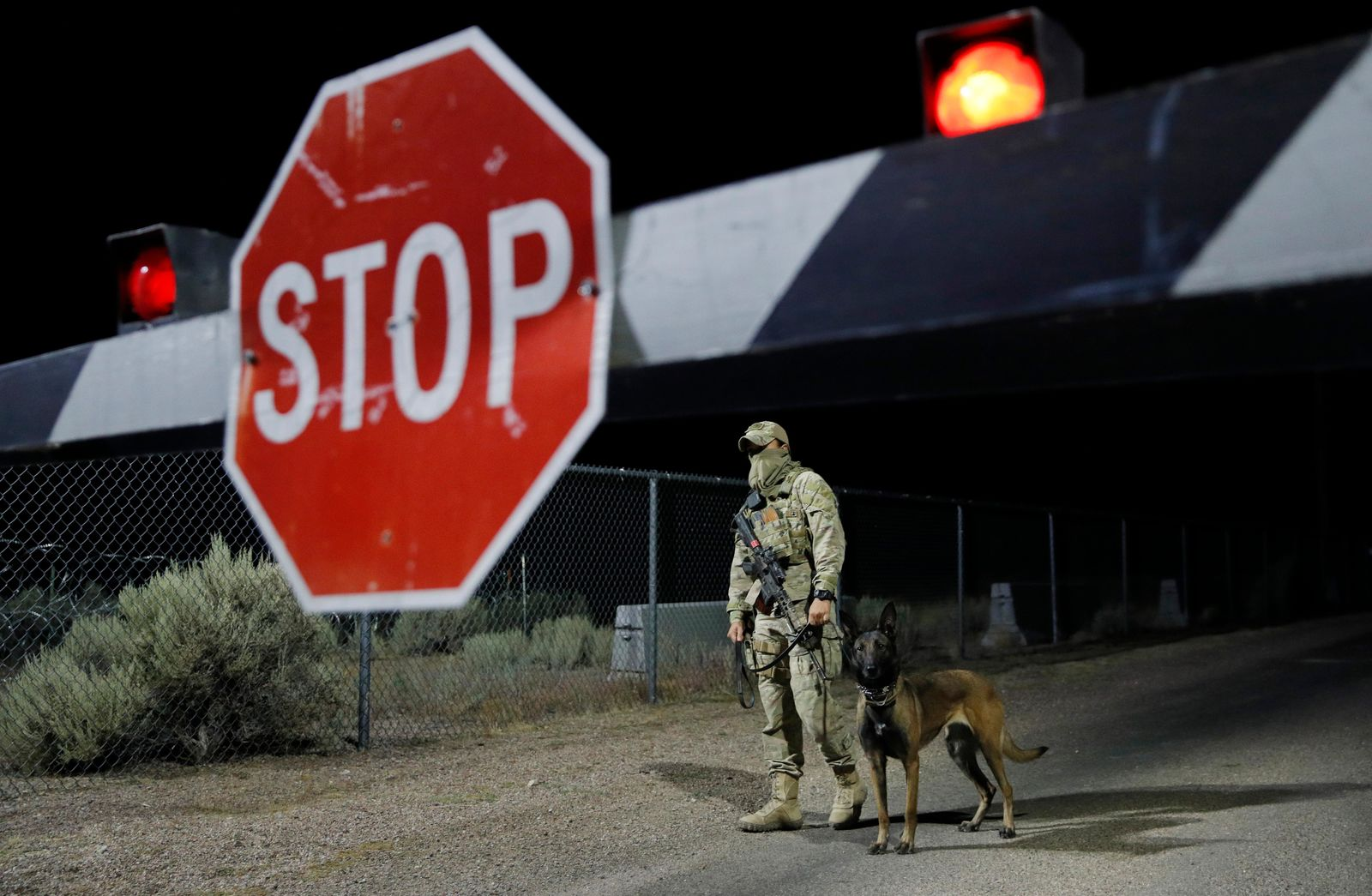 "A security guard stands at an entrance to the Nevada Test and Training Range near Area 51 Friday, Sept. 20, 2019, near Rachel, Nev. People gathered at the gate inspired by the ""Storm Area 51"" internet hoax. (AP Photo/John Locher)"