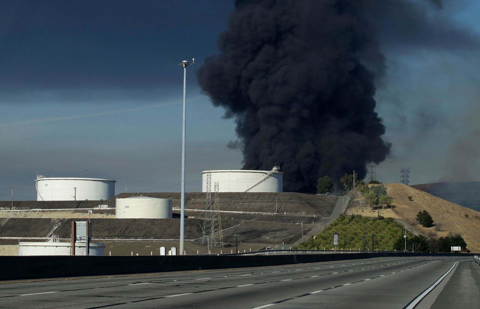 "Interstate 80 is closed as a fire at an oil storage facility burns Tuesday, Oct. 15, 2019, in Crockett, Calif. A fire burning at NuStar Energy LP facility prompted a hazardous materials emergency that led authorities to order the residents of two communities, including Rodeo, to stay inside with all windows and doors closed. ""This is a very dynamic, rapidly evolving situation,"" Capt. George Laing of the Contra Costa Fire Department said.  (AP Photo/Ben Margot)"