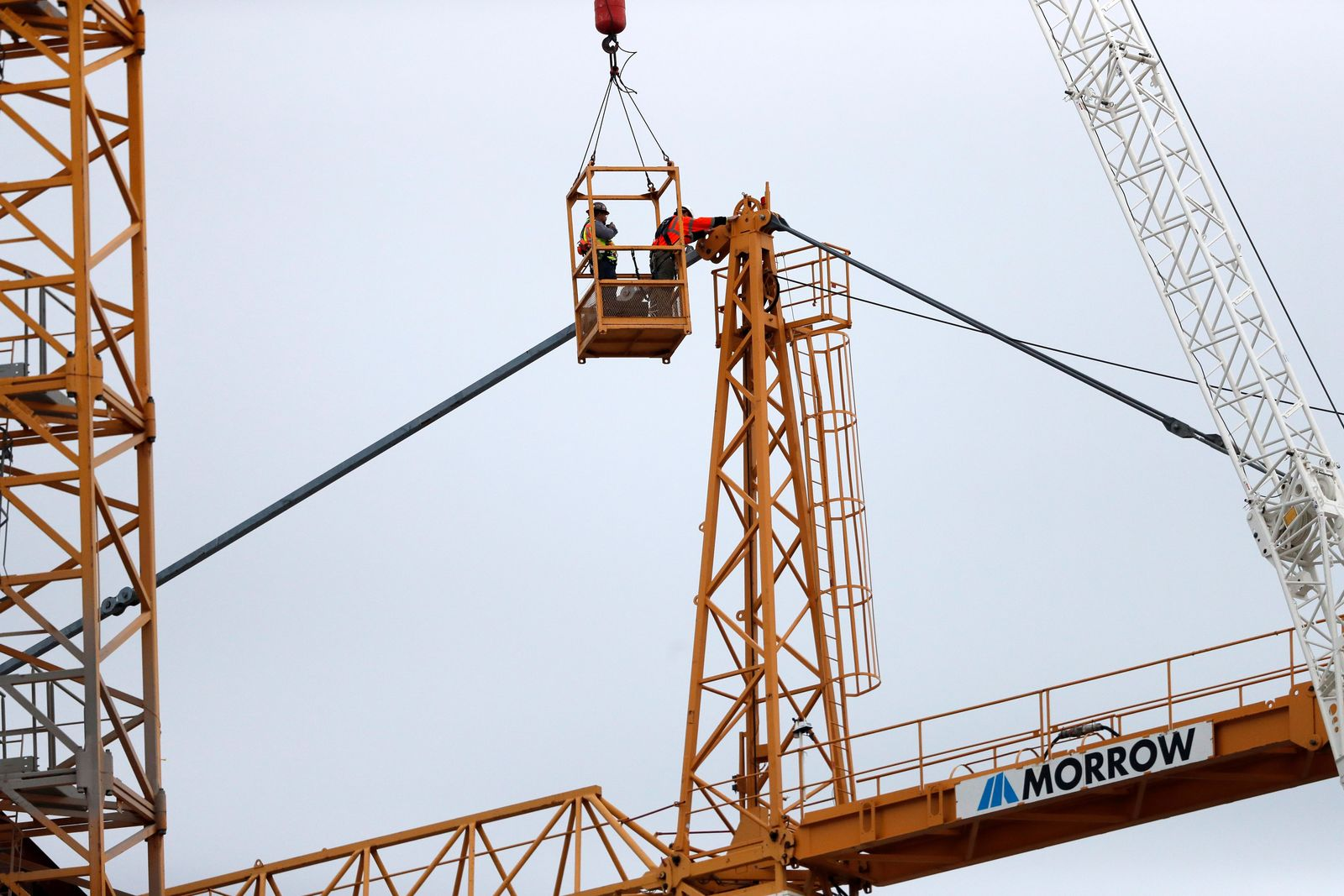 Workers in a bucket hoisted by a crane begin the process of preparing the two unstable cranes for implosion at the collapse site of the Hard Rock Hotel, which underwent a partial, major collapse while under construction last Sat., Oct., 12, in New Orleans, Friday, Oct. 18, 2019. (AP Photo/Gerald Herbert)