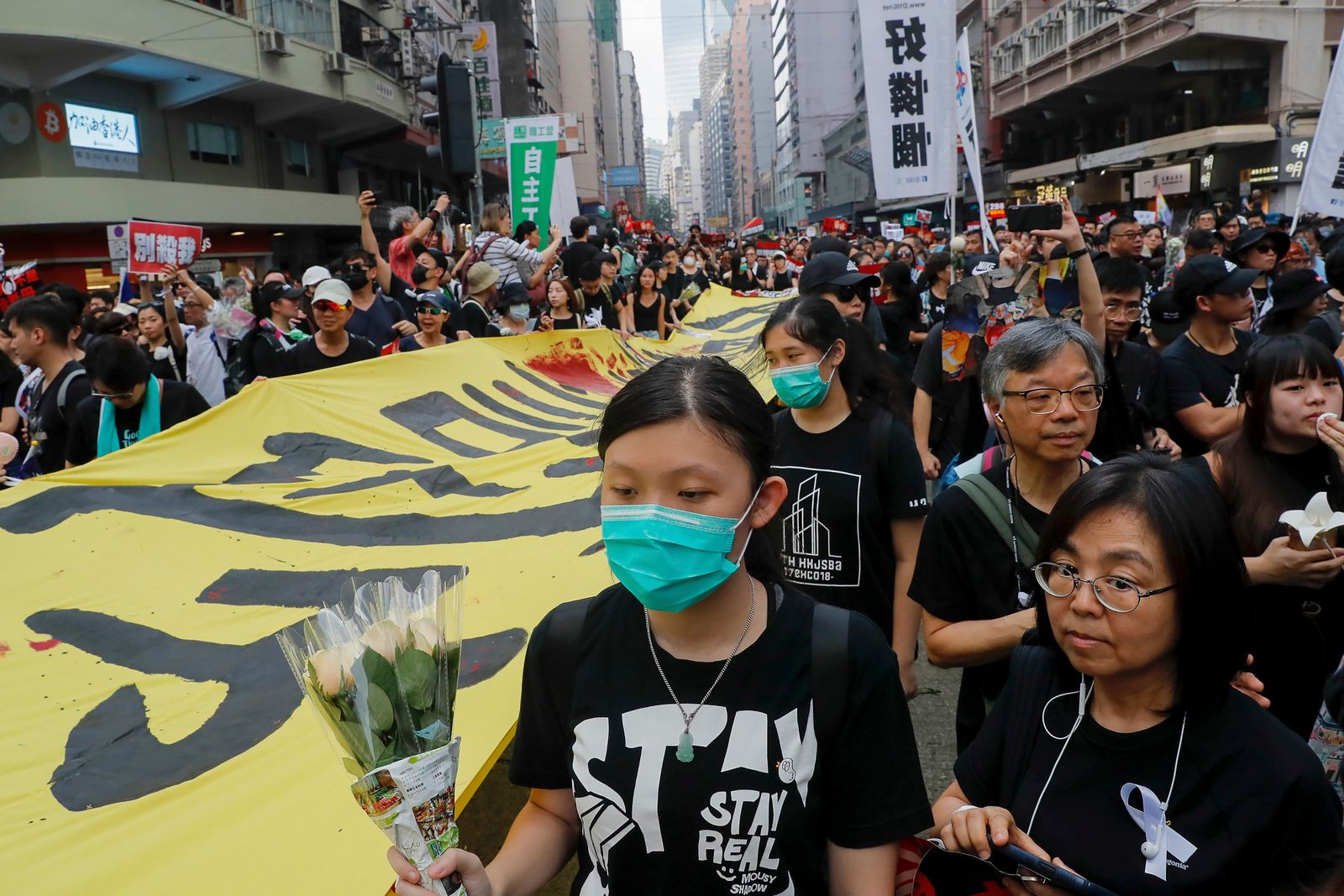 Tens of thousands of protesters carry posters and banners march through the streets as they continue to protest an extradition bill, Sunday, June 16, 2019, in Hong Kong (AP Photo/Kin Cheung)