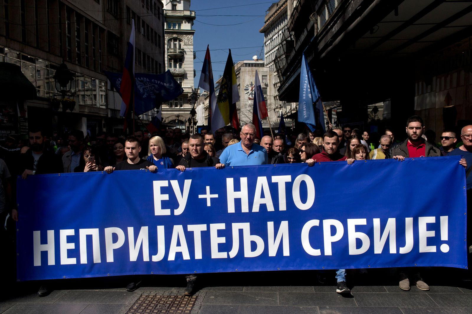 Vojislav Seselj, center, the leader of the ultranationalist Serbian Radical Party, and his supporters, march along a street during a protest in Belgrade, Serbia, Sunday, March 24, 2019.{ } (AP Photo/Marko Drobnjakovic)