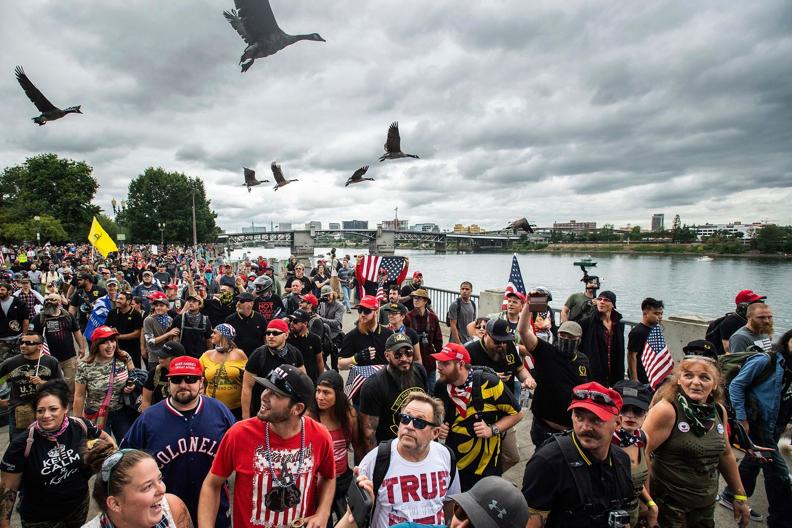 "Members of the Proud Boys and other right-wing demonstrators march along the Willamette River during an ""End Domestic Terrorism"" rally in Portland, Ore., on Saturday, Aug. 17, 2019. Police have mobilized to prevent clashes between conservative groups and counter-protesters who converged on the city. (AP Photo/Noah Berger)"