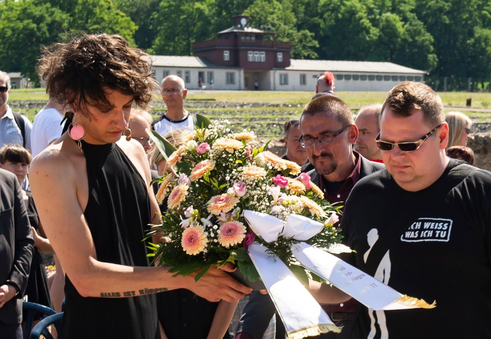 People lay a wreath in remembrance for prisoners assigned a pink triangle in the former Nazi concentration camp Buchenwald within the Christopher Street Day in Weimar, Germany, Sunday, June 23, 2019. There were 650 prisoners assigned a pink triangle in the Buchenwald concentration camp between 1937 and 1945. Many of them lost their lives. (AP Photo/Jens Meyer)