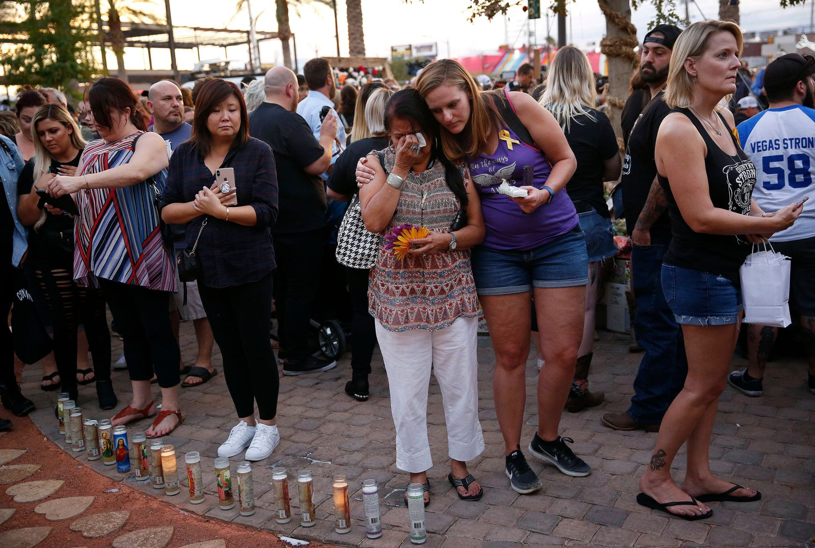 FILE - In this Monday, Oct. 1, 2018 file photo people embrace before a ceremony at a memorial garden, on the anniversary of the mass shooting a year earlier, in Las Vegas. (AP Photo/John Locher,File)