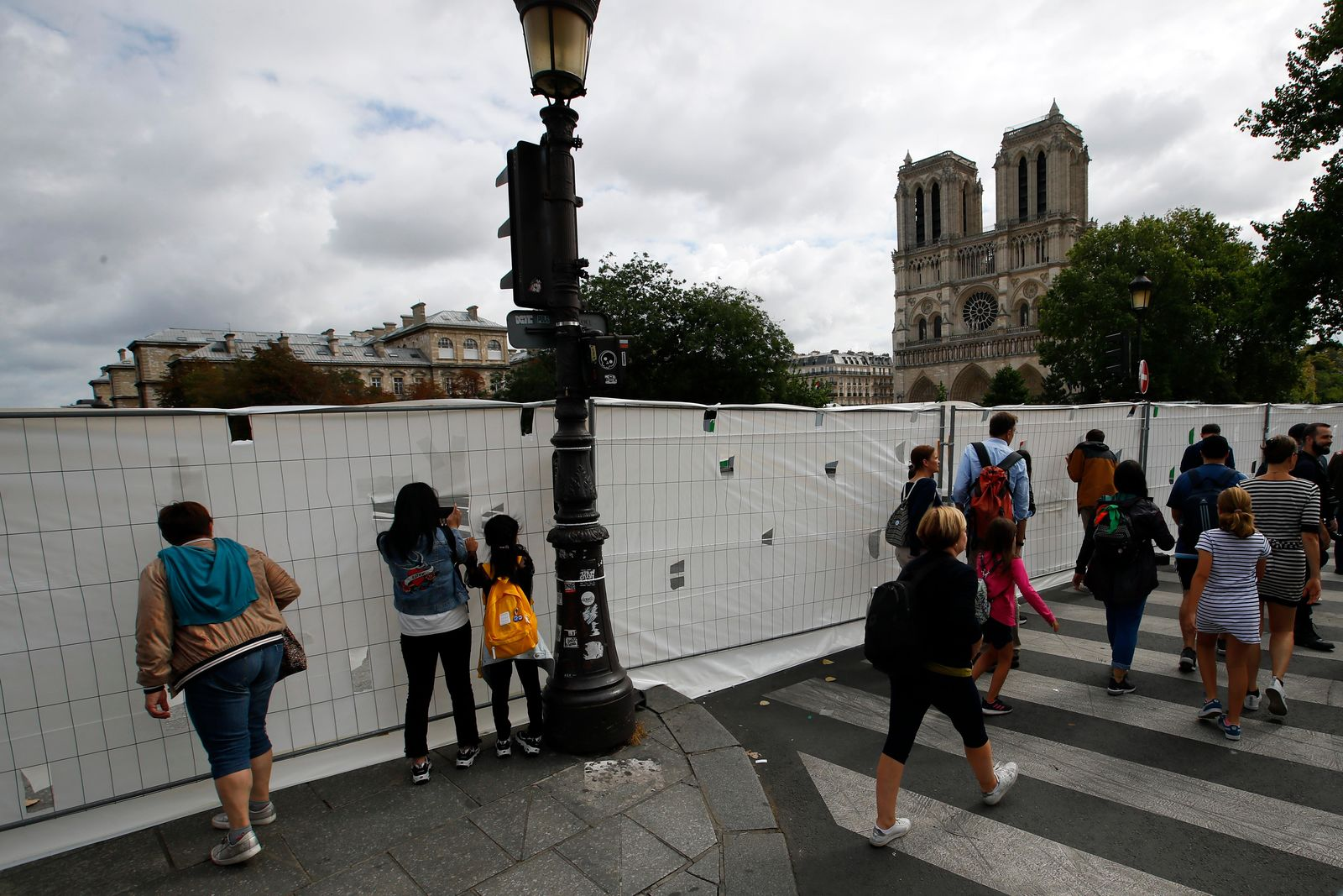 Tourists peer through protection panels securing a perimeter around the Notre Dame Cathedral ahead of the start of a massive lead decontamination in Paris, Thursday, Aug. 15, 2019. (AP Photo/Francois Mori)