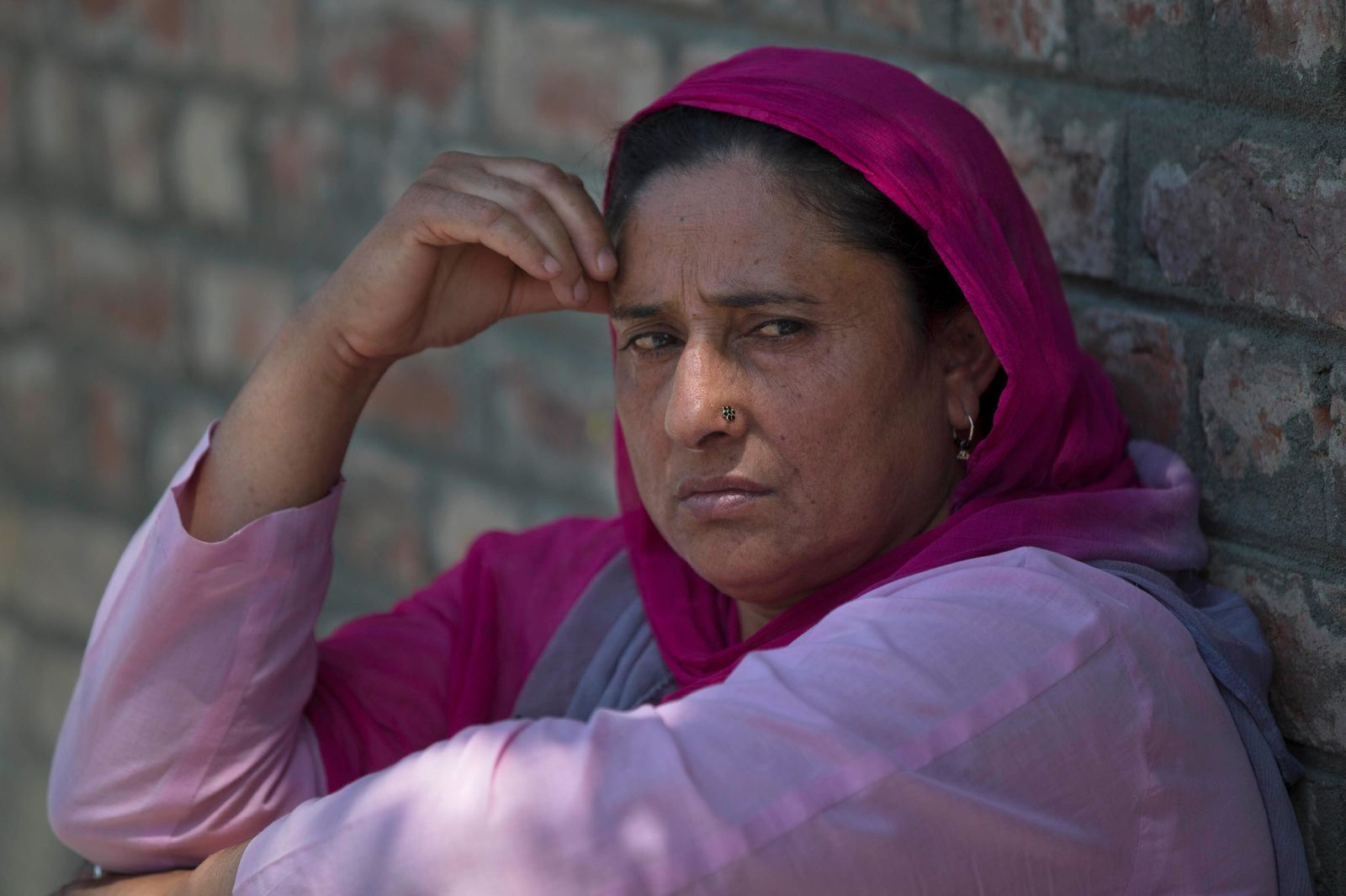 A Kashmiri woman sits on a footpath outside a police station waiting to hear the news about her relative who was detained during night raids in Srinagar, Indian controlled Kashmir, Tuesday, Aug. 20, 2019. Authorities say thousands of people, mostly young male protesters, have been arrested and detained in Indian-administered Kashmir amid an ongoing communications blackout and security lockdown. (AP Photo/ Dar Yasin)